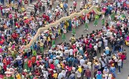 与五颜六色的龙的汉语灯节,狮子,旗子,汽车,在街道被吸引的人群前进了 库存图片