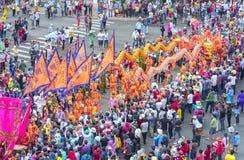 与五颜六色的龙的汉语灯节,狮子,旗子,汽车,在街道被吸引的人群前进了 免版税库存图片