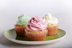 与五颜六色的结霜和装饰的杯形蛋糕 免版税图库摄影