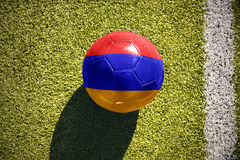 与亚美尼亚的国旗的橄榄球球在领域说谎 免版税库存图片
