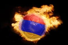 与亚美尼亚的旗子的橄榄球球火的 库存照片