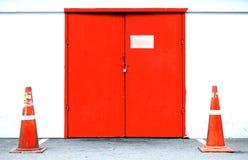 与交通锥体的工业外部红色门 库存图片