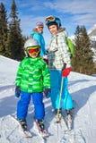 与享受冬天假期的母亲的两个孩子 免版税库存图片