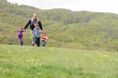 与享受在自然backg的三个孩子的家庭业余时间 免版税库存图片