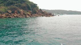 与亭亭玉立的女孩身分的美丽的景色在海滩的石头 股票视频