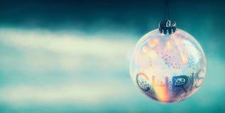 与亮光的透明圣诞节在蓝色轻的背景的球和bokeh 免版税库存图片