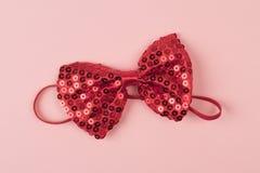 与亮晶晶的小东西的红色蝶形领结在浅粉红色的背景 库存图片