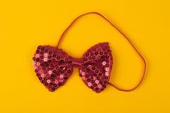 与亮晶晶的小东西的红色蝶形领结在淡黄色背景 库存图片