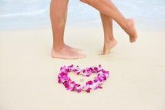 与亲吻的夫妇脚的海滩婚礼圆环 免版税库存照片