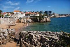 与人和别墅的多岩石的海滩 免版税库存图片