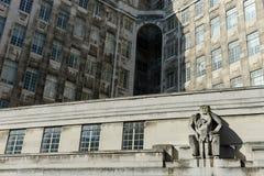与人和孩子的雕塑的一个大厦门面 图库摄影
