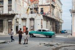与人和经典汽车的古巴街道场面 图库摄影