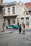 与人和经典汽车的古巴街道场面 免版税库存照片