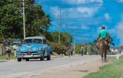 与人和经典汽车的街道风景在从古巴- Serie Kuba 2016年报告文学的乡下 免版税库存照片