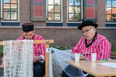 与人的荷兰市场修理捕鱼网的传统衣物的 免版税库存图片