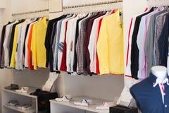 与人衬衣的服装店在挂衣架 免版税库存图片