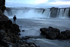 与人身分剪影的著名冰岛瀑布Godafoss  图库摄影
