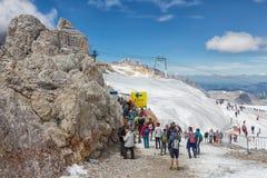 与人输入的索桥的Dachstein冰川在两座山之间 免版税库存照片