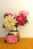 与人造丝花牡丹的美丽的花束在罐头白色和黄色背景中 免版税库存照片