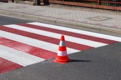 与仍然没变干的红色的跨装饰的行人交叉路 交通的制约由路标的 pedest更新的路 免版税图库摄影