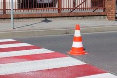 与仍然没变干的红色的跨装饰的行人交叉路 交通的制约由路标的 pedest更新的路 库存图片