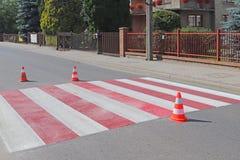 与仍然没变干的红色的跨装饰的行人交叉路 交通的制约由路标的 pedest更新的路 免版税库存图片
