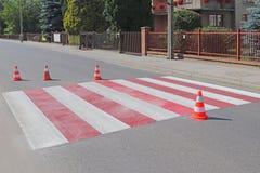 与仍然没变干的红色的跨装饰的行人交叉路 交通的制约由路标的 pedest更新的路 免版税库存照片