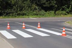 与仍然没变干的红色的跨装饰的行人交叉路 交通的制约由路标的 pedest更新的路 库存照片