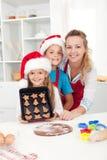 与他们的做圣诞节曲奇饼的母亲的孩子 库存图片