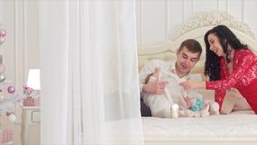 与他们的女儿的HD年轻家庭在床上在演播室 股票录像