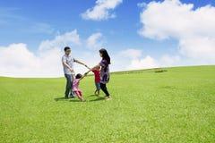与他们的孩子的父母戏剧在公园 免版税库存图片
