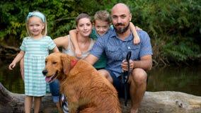 与他们的爱犬的美丽的年轻家庭,金毛猎犬 免版税库存图片