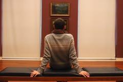 与他的后面坐沙发和看绘画图片的未知的人在美术馆,欧洲 免版税图库摄影