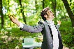 与他的商人在他的办公室前面的绿色公园武装大开 到达天空的企业概念金黄回归键所有权 免版税库存照片