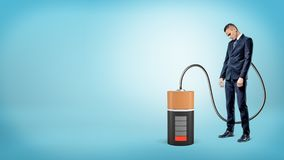 与他的头的一个哀伤的商人下来站立连接由缆绳到一个大空的电池 免版税库存图片