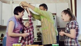 与他的家庭的父亲笑话在厨房里,当烹调从面团时的食物 股票录像