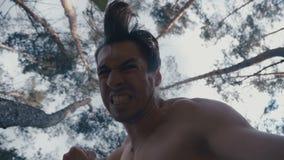 与他的拳头的疯狂的积极的赤裸上身的人敲打说谎的人室外在森林 影视素材