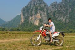 与他的摩托车越野赛的一个未认出的车手在Vang Vieng,老挝的山背景中 图库摄影