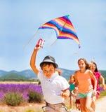 与他的朋友的愉快的男孩飞行彩虹风筝 库存图片