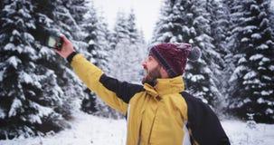 与他的电话的吸引人和悦目旅游作为selfies在多雪的森林中间在冬日,非常 股票视频