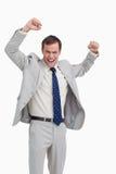 与他的胳膊的欢呼的生意人 免版税图库摄影