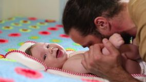 与他的说谎在床上的婴儿的有胡子的父亲千福年的戏剧 概念父亲和儿子 一个人和新出生 股票视频