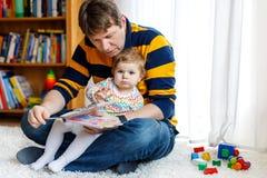 与他逗人喜爱的可爱的小女儿女孩的年轻父亲阅读书 库存图片