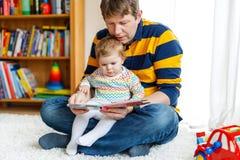 与他逗人喜爱的可爱的小女儿女孩的年轻父亲阅读书 库存照片