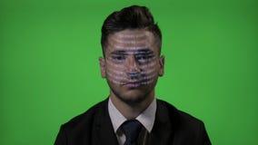 与代码的年轻可爱的商人在面孔工作作为在绿色屏幕背景的一个计算机程序设计者- 股票录像