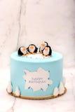 与企鹅的生日蛋糕在石背景 库存照片