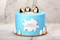 与企鹅的生日蛋糕在石背景 库存图片