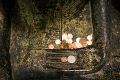与优点硬币金钱的坐的菩萨雕象在佛教寺庙的菩萨的手上 在泰语的佛教捐赠他们的金钱为 免版税库存图片
