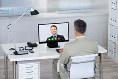 与伙伴的商人电视电话会议在书桌的计算机上 库存照片