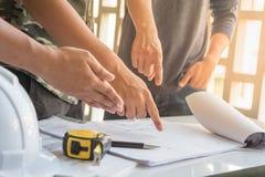 与伙伴的工程师会议的图象批准的建筑项目的,工作和在工作场所的工程学工具 免版税库存照片